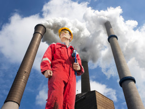 Engineer looking up towards the wind direction with tall smoke stacks, emitting vaporized water, seen from below