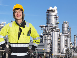 Happy, proud and confident chemical engineer smiling into the camera in front of a petrochemical plabnt, with stainless steel crackers, destillation towers, and a couple of smoke stacks in the background